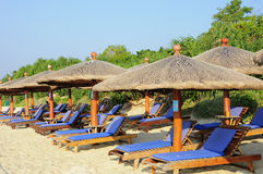 Reedregenschirm-und Strand-Stuhl stockbilder