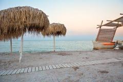 REEDregenschirme auf dem Strand im Sonnenuntergang stockfotografie