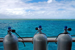 Reef diving. Three scuba cylinders, green water, great barrier reef Royalty Free Stock Photos