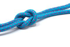 Reef knot on a blue rope. With pink and purple highlights, isolated on a white background Royalty Free Stock Image