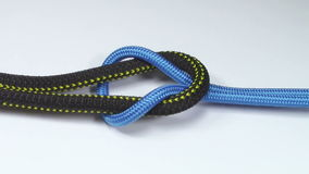 Reef knot tying. Reef knot made from two different synthetic ropes , tied on white background stock footage