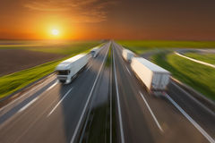 Reefer trucks in motion blur on the empty freeway at sunset