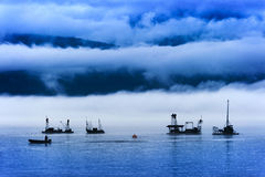 Reefnet Salmon Fishermen on a Foggy Day. Pacific salmon fishermen off of Lummi Island in the Puget Sound area of Washington State. Reefnetting is an old Indian Stock Photos