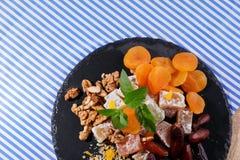 Reeks banketbakkerijingrediënten Een plaat met Turkse verrukking en vruchten op een stoffenachtergrond Voedzame desserts stock foto