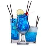 Reeks blauwe cocktails met decoratie van vruchten en kleurrijk die stro op witte achtergrond worden geïsoleerd Stock Foto's