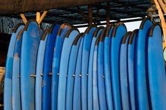 Reeks blauwe kleuren zachte surfplanken in een stapel door oceaan bali indonesië Brandingsraad op zandig strand voor huur r stock afbeelding