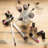 Reeks borstels en lippenstiften voor make-up op houten achtergrond Royalty-vrije Stock Afbeeldingen