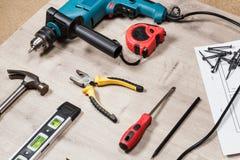 Reeks bouwhulpmiddelen aan reparatie op een houten oppervlakte: boor, hamer, buigtang, self-tapping schroeven, roulette, niveau Stock Foto