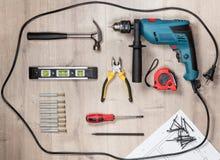Reeks bouwhulpmiddelen aan reparatie op een houten oppervlakte: boor, hamer, buigtang, self-tapping schroeven, roulette, niveau Stock Foto's