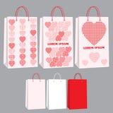 Reeks document zakken en pakketten in roze kleur met patronen Malplaatjespakketten in rood, wit en roze Royalty-vrije Stock Foto's