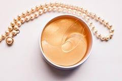 Reeks gouden anti het verouderen oogflarden in de plastic kruik en parelhalsband stock foto
