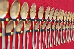 Reeks Gouden lepels op rode achtergrond stock afbeelding