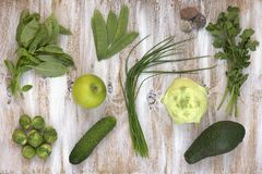 Reeks groene groenten op witte geschilderde houten achtergrond: koolraap, avocado, spruitjes, appel, komkommer, groene ui, erwt Royalty-vrije Stock Fotografie