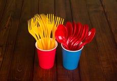 Reeks heldere beschikbare lepels en vorken in plastic koppen, op achtergrond van houten lijst Stock Foto's