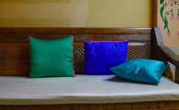 Reeks hoofdkussens op houten bank bij woonkamer stock afbeeldingen