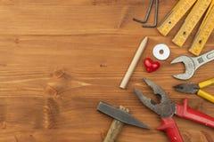Reeks hulpmiddelen en instrumenten op houten achtergrond Verschillende soorten hulpmiddelen voor huishoudenkarweien De reparaties Stock Foto