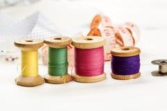 Reeks hulpmiddelen en toebehoren voor het naaien en handwerk met draden in spoelen, naalden, die band en andere punten op een wit royalty-vrije stock foto's