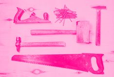 Reeks hulpmiddelen om aan hout te werken - zaag, vliegtuig, hamers, houten hamer, spijkers Gestemd roze royalty-vrije stock afbeeldingen