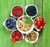 Reeks ingrediënten voor een gezond voedselontbijt - muesli, vers en gedroogd fruit, noten, goji Stock Afbeeldingen