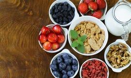 Reeks ingrediënten voor een gezond voedselontbijt - muesli, vers en gedroogd fruit, noten, goji Royalty-vrije Stock Afbeelding