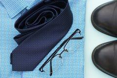 Reeks kleren en toebehoren voor de mens op blauw achtergrond, zaken of bureauconcept stock afbeeldingen