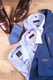 Reeks kleren van klassieke mensen - blauw kostuum, overhemden, bruine schoenen, riem en band op houten achtergrond Stock Foto