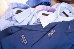 Reeks kleren van klassieke mensen - blauw kostuum, overhemden, bruine schoenen, riem en band op houten achtergrond Royalty-vrije Stock Foto's