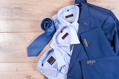 Reeks kleren van klassieke mensen - blauw kostuum, overhemden, bruine schoenen, riem en band op houten achtergrond Stock Foto's