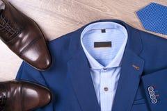 Reeks kleren van klassieke mensen - blauw kostuum, overhemden, bruine schoenen, riem en band op houten achtergrond Stock Afbeelding