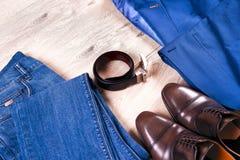 Reeks kleren van klassieke mensen - blauw kostuum, overhemden, bruine schoenen, riem en band op houten achtergrond Royalty-vrije Stock Fotografie