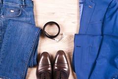 Reeks kleren van klassieke mensen - blauw kostuum, overhemden, bruine schoenen, riem en band op houten achtergrond Royalty-vrije Stock Afbeeldingen