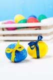 Reeks kleurrijke paaseieren in een witte houten doos op blauwe achtergronden Stock Afbeeldingen