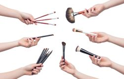 Reeks kosmetische borstels voor make-up in vrouwelijke handen royalty-vrije stock foto's