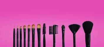 Reeks make-upborstels op gekleurde samengestelde achtergrond stock afbeelding