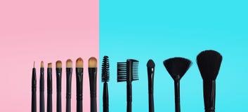 Reeks make-upborstels op gekleurde samengestelde achtergrond stock afbeeldingen