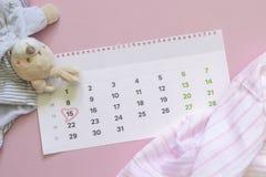 Reeks pasgeboren toebehoren in afwachting van kind - kalender met omcirkeld nummer 15 vijftien, babykleren, speelgoed op roze stock fotografie