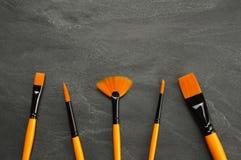 Reeks penselen op zwarte steenachtergrond met exemplaarruimte stock afbeelding
