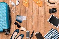 Reeks reistoebehoren op houten vloer Reisachtergrond met bagage, schoenen, paspoorten, wipschakelaars, hoed, camera Royalty-vrije Stock Foto's