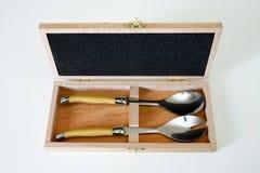 Reeks saladelepels in houten geval. Stock Afbeeldingen