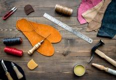Reeks schoenmakershulpmiddelen op bruine houten bureau hoogste mening als achtergrond stock afbeeldingen