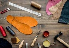 Reeks schoenmakershulpmiddelen op bruine houten bureau hoogste mening als achtergrond royalty-vrije stock foto's
