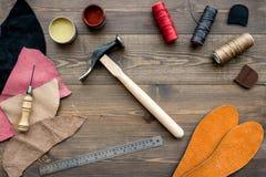Reeks schoenmakershulpmiddelen op bruine houten bureau hoogste mening als achtergrond royalty-vrije stock afbeeldingen