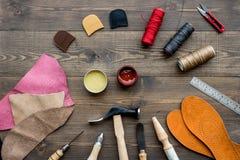 Reeks schoenmakershulpmiddelen op bruine houten bureau hoogste mening als achtergrond royalty-vrije stock foto
