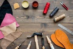 Reeks schoenmakershulpmiddelen op bruine houten bureau hoogste mening als achtergrond copyspace stock afbeeldingen