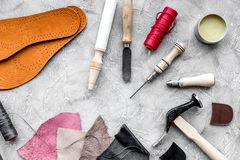 Reeks schoenmakershulpmiddelen op grijze van het steenbureau hoogste mening als achtergrond royalty-vrije stock fotografie