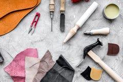 Reeks schoenmakershulpmiddelen op grijze van het steenbureau hoogste mening als achtergrond stock afbeeldingen