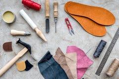 Reeks schoenmakershulpmiddelen op grijze van het steenbureau hoogste mening als achtergrond stock foto's