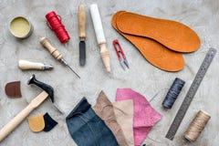 Reeks schoenmakershulpmiddelen op grijze van het steenbureau hoogste mening als achtergrond stock afbeelding