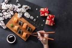 Reeks sushi en makibroodjes, hand met eetstokjes, giftvakjes en tak van witte bloemen op steenlijst stock foto's