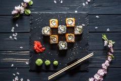Reeks sushi op een zwarte hoogste mening als achtergrond stock foto's